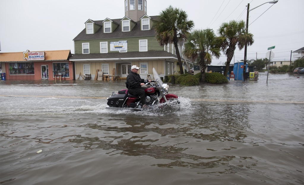 A motorcyclist navigates through flood waters in Garden City Beach, South Carolina, October 2, 2015. Category 4 Hurricane Joaquin is now moving northward and has started bringing swells to parts of the southeastern coast of the United States, the National Hurricane Center said on Friday. REUTERS/Randall Hill - RTS2SHJ