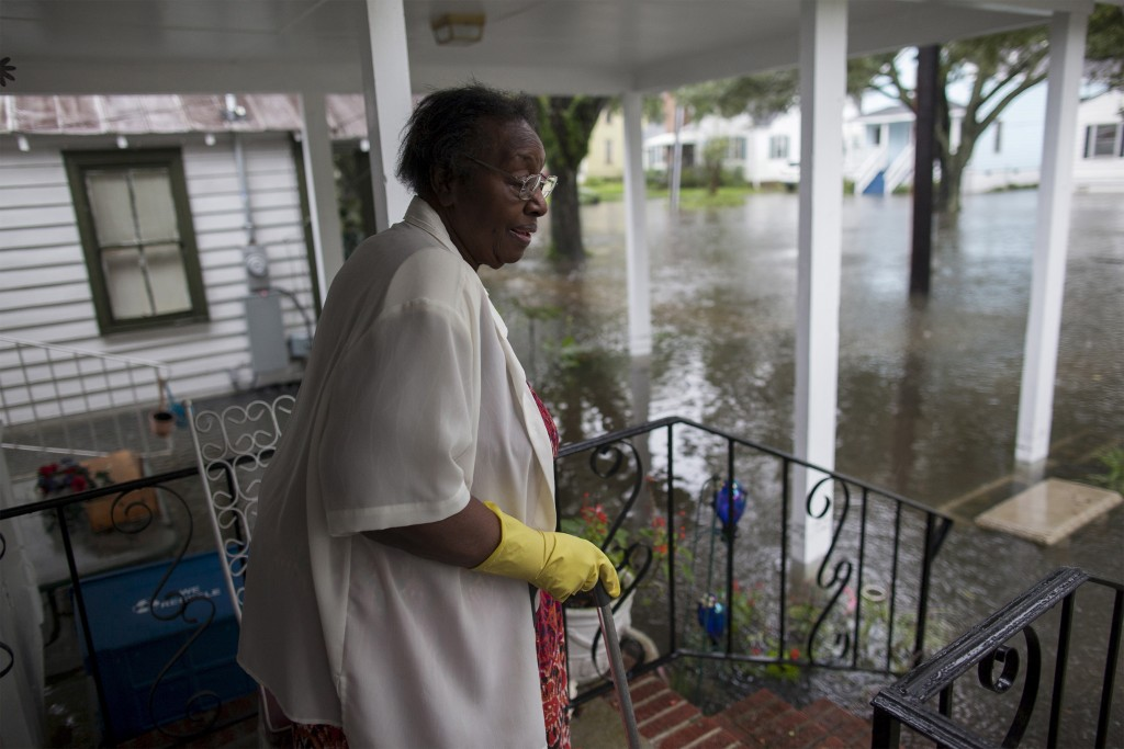 Ammie McKnight watches the level of floodwaters in the front yard of her Orange Street home in Georgetown, South Carolina October 4, 2015. Most major roads through the historical South Carolina city have closed due to flooding. Vast swaths of U.S. Southeast and mid-Atlantic states were grappling with heavy rains and flooding from a separate weather system which has already caused at least five deaths, washed out roads and prompted evacuations and flash flood warnings. REUTERS/Randall Hill - RTS2ZBO