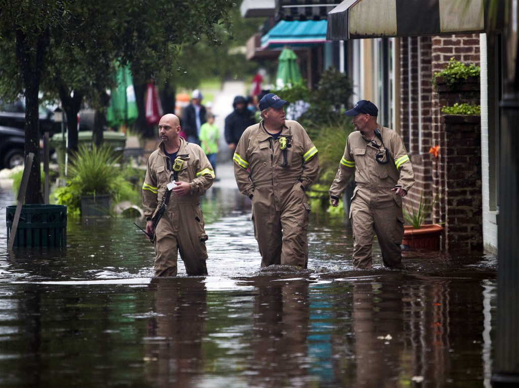 (L-R) Norman Beauregard, Kevin Attender and Chris Rogers of the Georgetown Fire Department, wade through flooded Front Street in Georgetown, South Carolina October 4, 2015. Most major roads through the historical South Carolina city have closed due to flooding. Vast swaths of U.S. Southeast and mid-Atlantic states were grappling with heavy rains and flooding from a separate weather system which has already caused at least five deaths, washed out roads and prompted evacuations and flash flood warnings. REUTERS/Randall Hill - RTS2ZXC