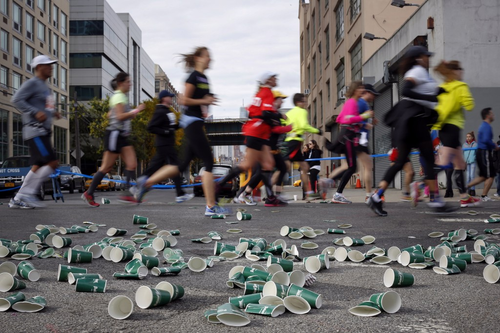 Discarded cups are seen along the route as runners make their way through the borough of Queens during the New York City Marathon in New York, November 3, 2013. REUTERS/Shannon Stapleton (UNITED STATES - Tags: SPORT ATHLETICS) - RTX14YWQ