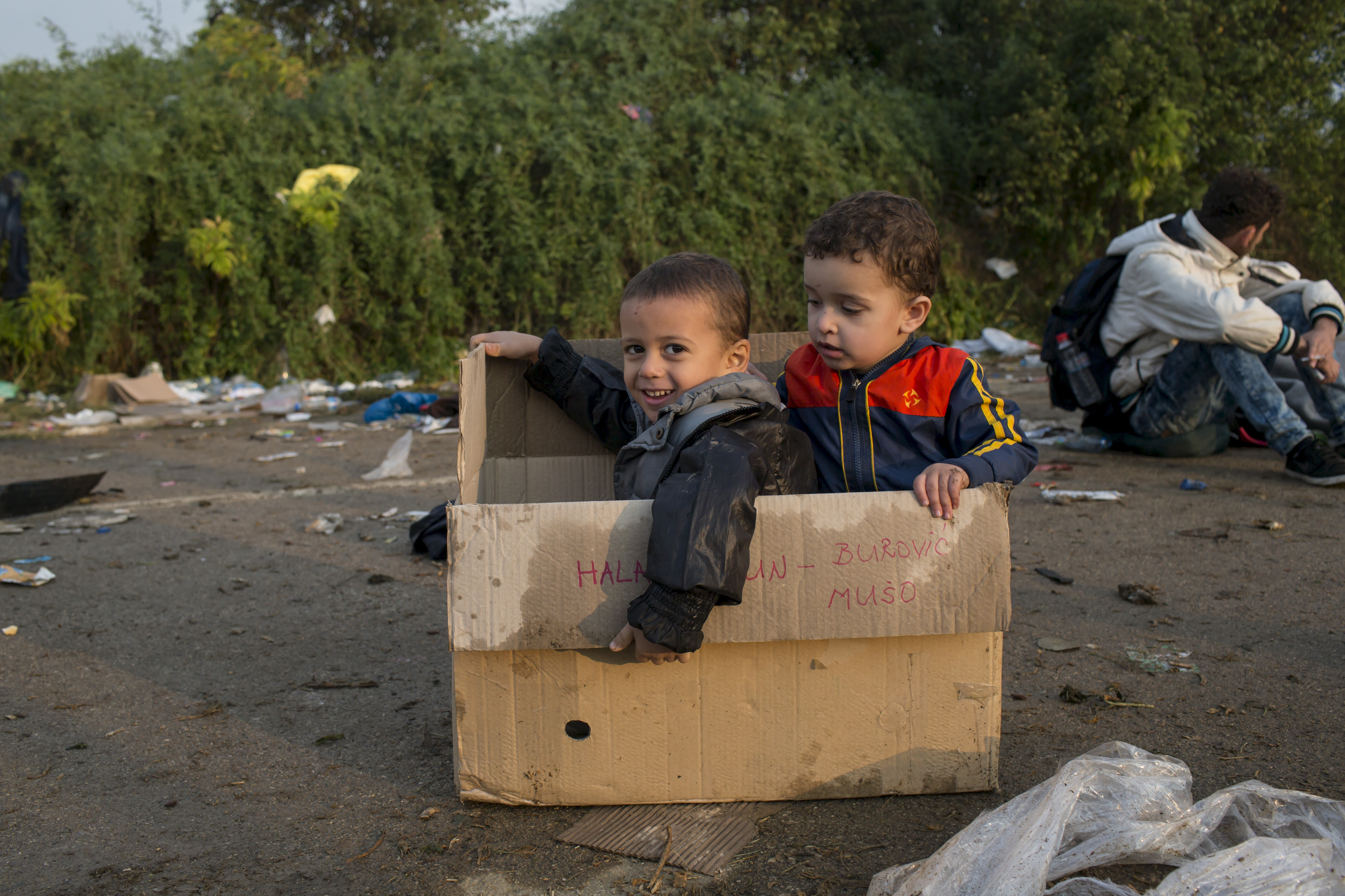 Children sit in a box as they wait to board buses after crossing the border with Serbia, near the village of Babska, Croatia, on Sept. 24, 2015. Photo by Marko Djurica/Reuters
