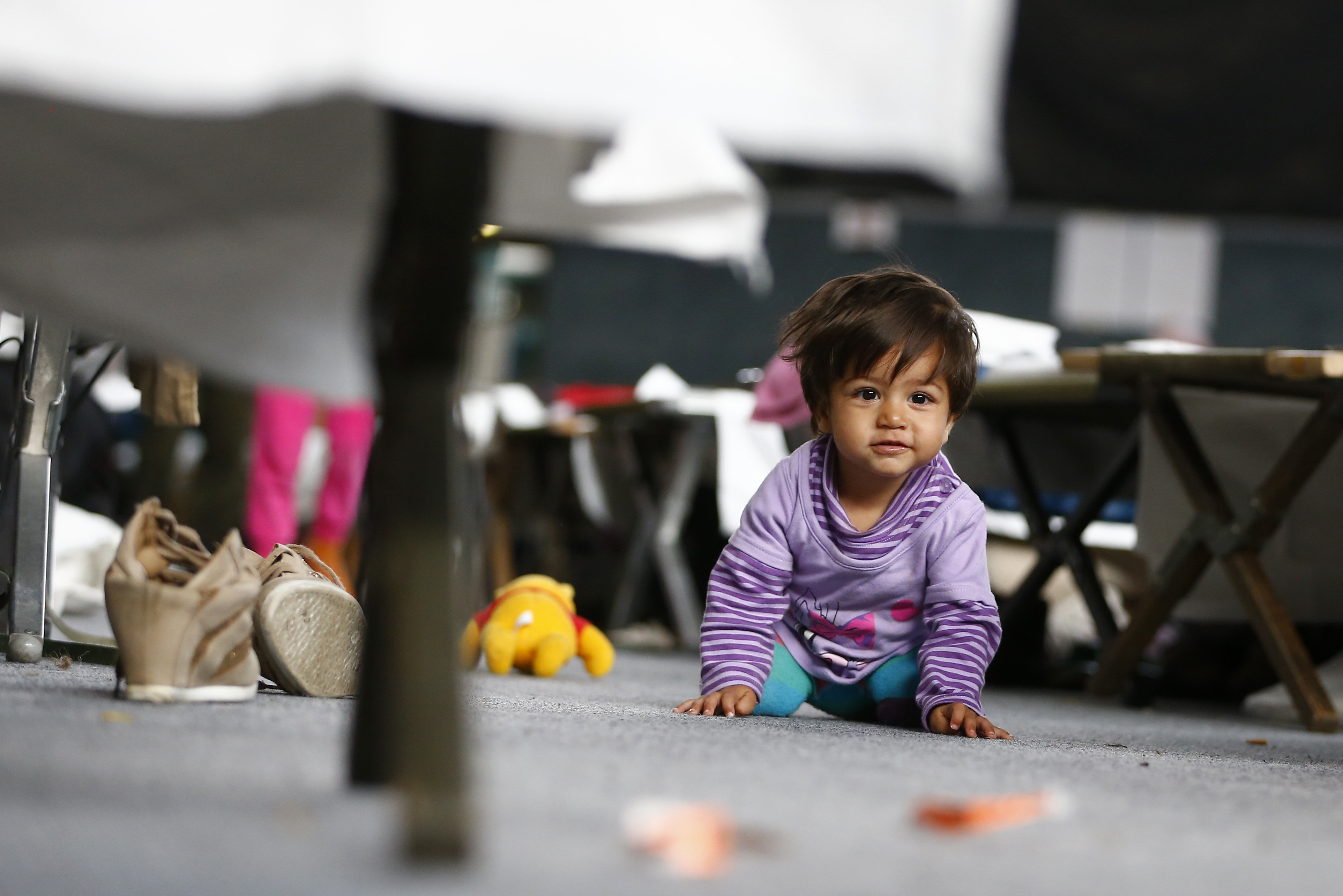 A migrant child looks on as it sits on the ground at an improvised temporary shelter in a sports hall in Hanau, Germany, on Sept. 24, 2015. Photo by Kai Pfaffenbach/Reuters