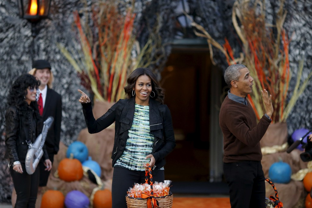 U.S. President Barack Obama and first lady Michelle Obama wave as they arrive at a Halloween trick-or-treating celebration on the South Lawn of the White House in Washington October 30, 2015.  REUTERS/Carlos Barria - RTX1U1KF