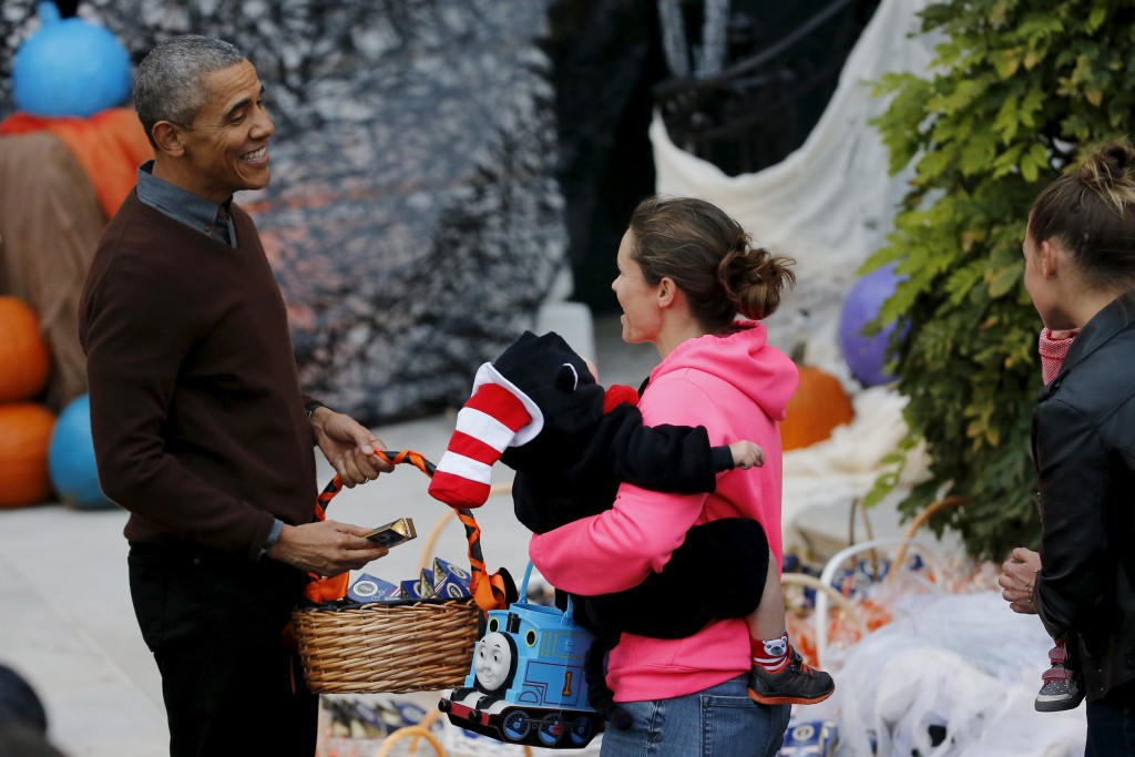 U.S. President Barack Obama smiles at a child during a Halloween trick-or-treating celebration on the South Lawn of the White House in Washington October 30, 2015.  REUTERS/Carlos Barria - RTX1U1KK