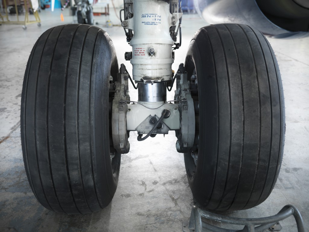 Close up of airplane wheels in hangar. Photo by Monty Rakusen