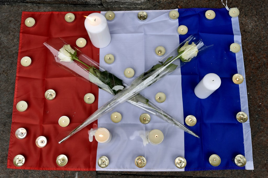 Candles and white roses are displayed on the French flag in  Toulouse on November 14, 2015 as a tribute to the victims of the attacks in Paris in which 128 people were killed.  Islamic State jihadists on Saturday claimed a series of coordinated attacks by gunmen and suicide bombers in Paris that killed at least 128 people in scenes of carnage at a concert hall, restaurants and the national stadium. Photo by Pascal Pavani/AFP/Getty Images