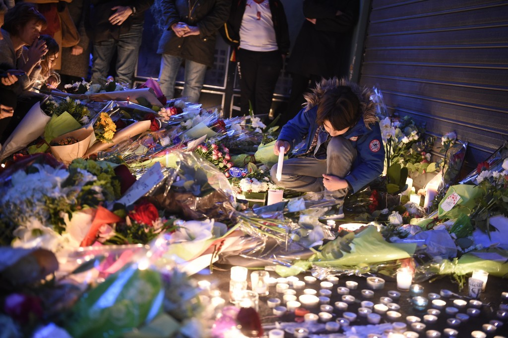 "A youth lights a candle as people lay floral tributes at the ""Belle Equipe"" restaurant, the site of one of the attacks in Paris on November 14, 2015.  Photo by Lionel Bonaventure/AFP/Getty Images"