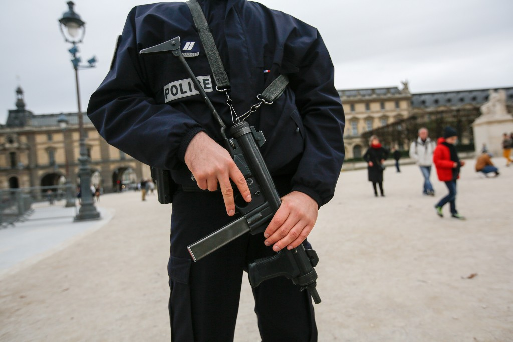 A police officer stands guard holding a gun at the Louvre museum in Paris, France, on Saturday, Nov. 14, 2015. French President Francois Hollande blamed Islamic State militants for coordinated strikes in Paris that left 127 dead, bringing the conflict with the radical group to the heart of the Western world. Photographer: Simon Dawson/Bloomberg via Getty Images