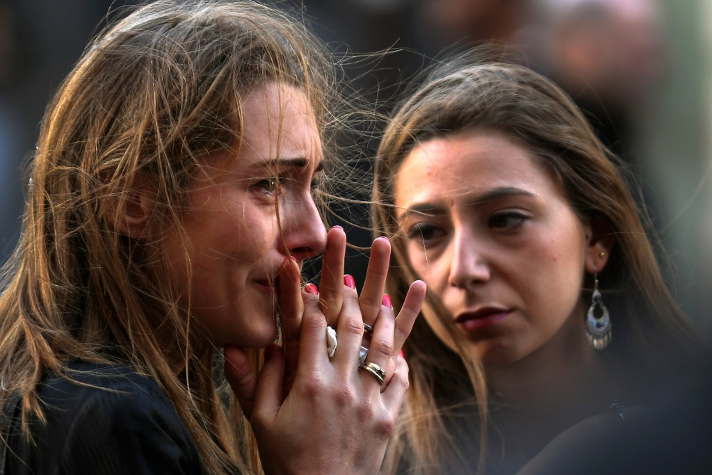 People react as they view tributes and flowers outside La Belle Equipe restaurant on Rue de Charonne following Fridays terrorist attack and France observes three days of national mourning on November 15, 2015 in Paris, France. As France observes three days of national mourning members of the public continue to pay tribute to the victims of Friday's deadly attacks. A special service for the families of the victims and survivors is to be held at Paris's Notre Dame Cathedral later on Sunday. Photo by Christopher Furlong/Getty Images