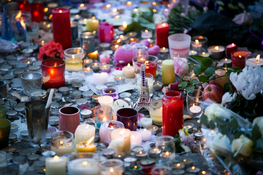 Candles are lit near the 'Bataclan' theatre as France observes three days of national mourning on November 15, 2015 in Paris, France. As France observes three days of national mourning members of the public continue to pay tribute to the victims of Friday's deadly attacks. A special service for the families of the victims and survivors is to be held at Paris's Notre Dame Cathedral later on Sunday. Photo by Marc Piasecki/Getty Images
