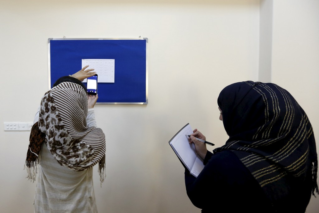 Afghan women mark their calendars as they attend a class of the country's first ever gender and women's studies Master's program in Kabul University, Afghanistan on Oct. 19. Photo by Mohammad Ismail/Reuters