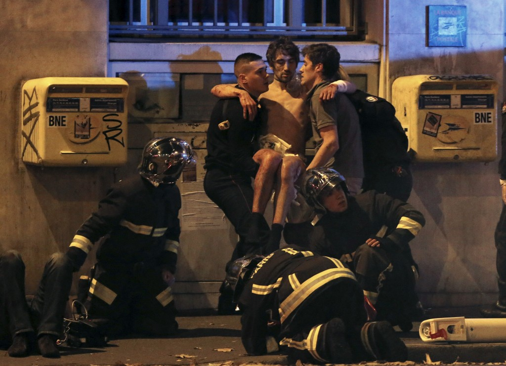 French fire brigade members aid an injured individual near the Bataclan concert hall following fatal shootings in Paris. Photo by Christian Hartmann/Reuters