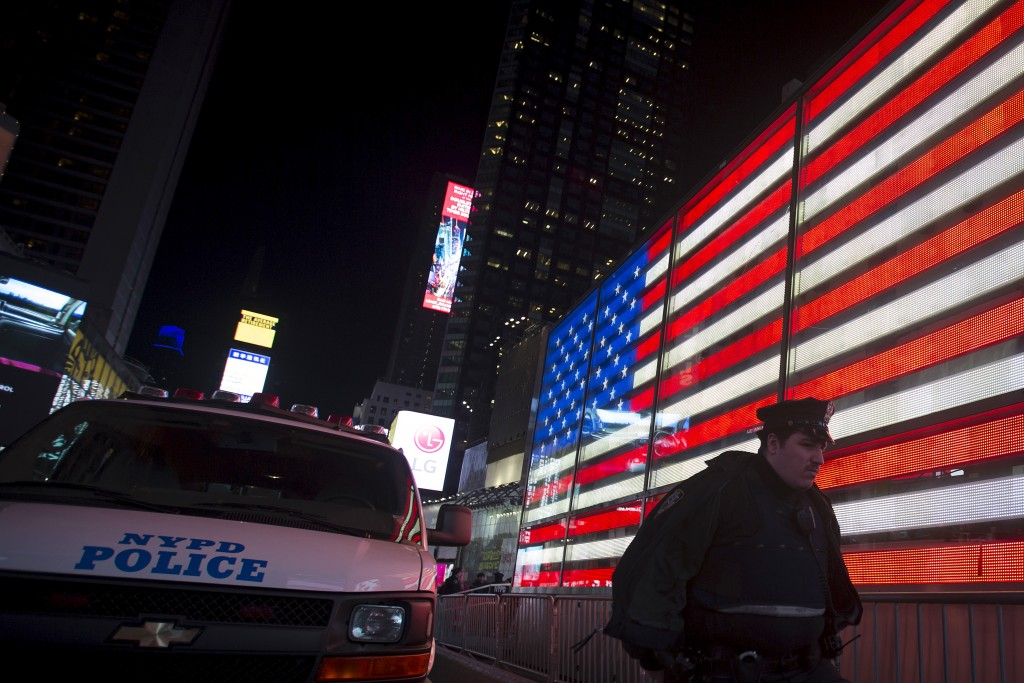 A New York City police officer walks from a van that was sent to Times Square to boost security Friday night, Manhattan, November 13, 2015. New York, Boston and other U.S. cities bolstered security on Friday night as a precautionary response to the Paris attacks. Photo by Carlo Allegri/Reuters