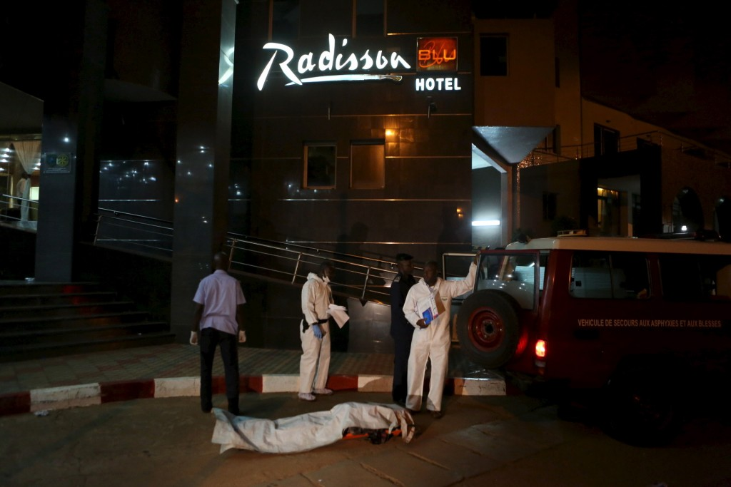 Malian officials prepare to lift a corpse into an emergency vehicle outside the Radisson hotel in Bamako, Mali, November 20, 2015. Photo by Joe Penney/Reuters.