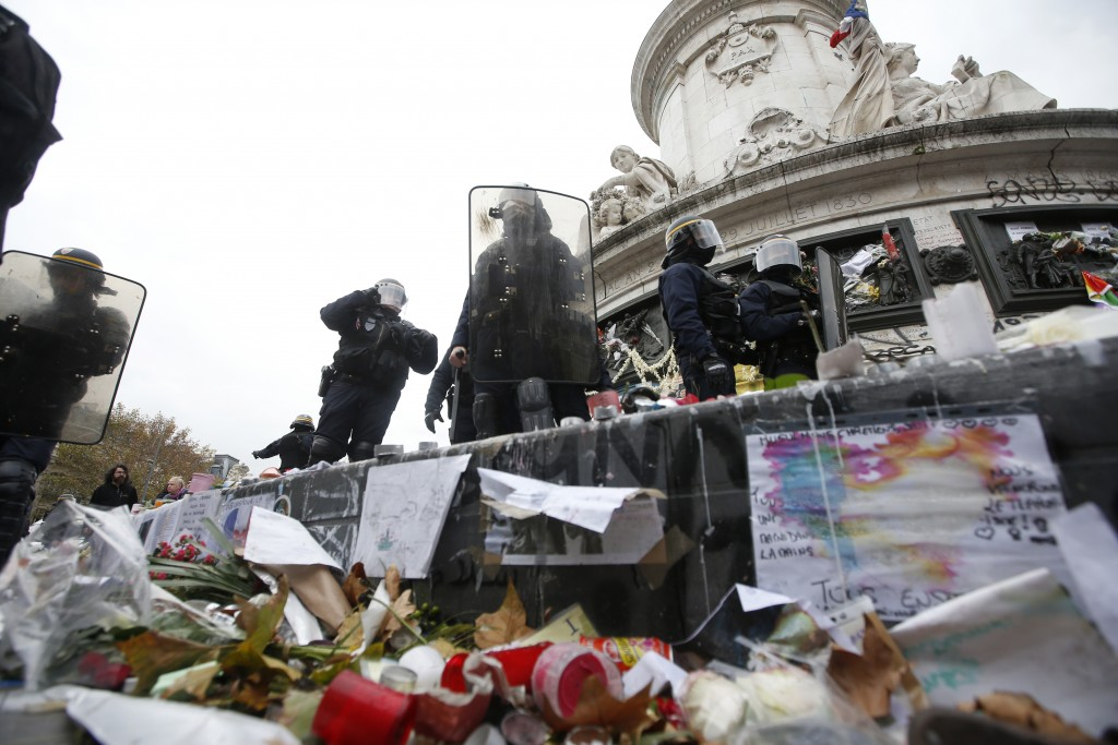 French CRS riot police stand on flowers, candles and messages by the statue at the Place de la Republique during clashes after the cancellation of a planned climate march following shootings in the French capital, ahead of the World Climate Change Conference 2015 (COP21), in Paris, France, November 29, 2015.   REUTERS/Eric Gaillard    - RTX1WCPL