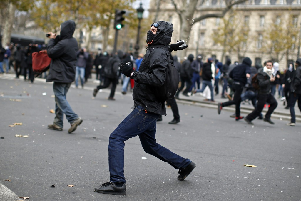 A demonstrator throws a projectile at French CRS riot police during clashes at the Place de la Republique after the cancellation of a planned climate march following shootings in the French capital, ahead of the World Climate Change Conference 2015 (COP21), in Paris, France, November 29, 2015. REUTERS/Benoit Tessier - RTX1WCVO