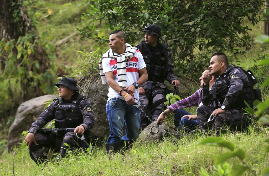 Prison guards escort handcuffed inmates, who are looking for a pit in a rural area close to Chaguani, Colombia, on June 18, 2015. Human rights advocates and families hope FARC rebels, like paramilitaries before them, will reveal grave locations as part of a deal which would allow them to avoid long prison terms and even enter politics. Victims' groups warn that unless more bodies are exhumed, identified and returned to loved ones, Colombia risks handicapping post-conflict development. Photo by Jose Miguel Gomez/Reuters