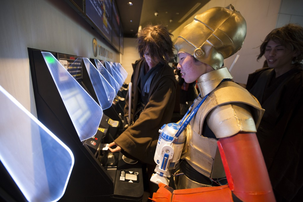 "A fan dressed as C-3PO purchases a ticket from a self-service machine ahead of the first public screening of Walt Disney Co.'s ""Star Wars: The Force Awakens"" at TOHO Cinemas Roppoing Hills in Tokyo, Japan, on Friday, Dec. 18, 2015. Photo by Tomohiro Ohsumi/Bloomberg via Getty Images."