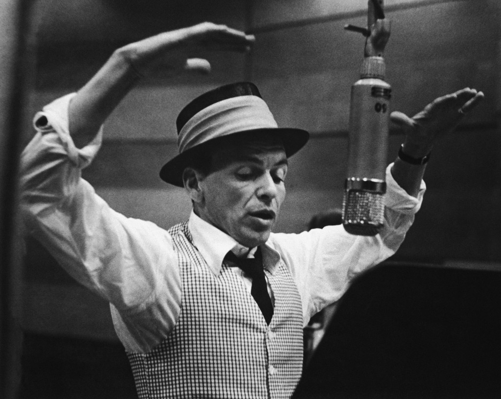 American singer and actor Frank Sinatra (1915 - 1998) gestures with his hands while singing into a microphone during a recording session in a studio at Capitol Records, early 1950s. (Photo by Murray Garrett/Getty Images)