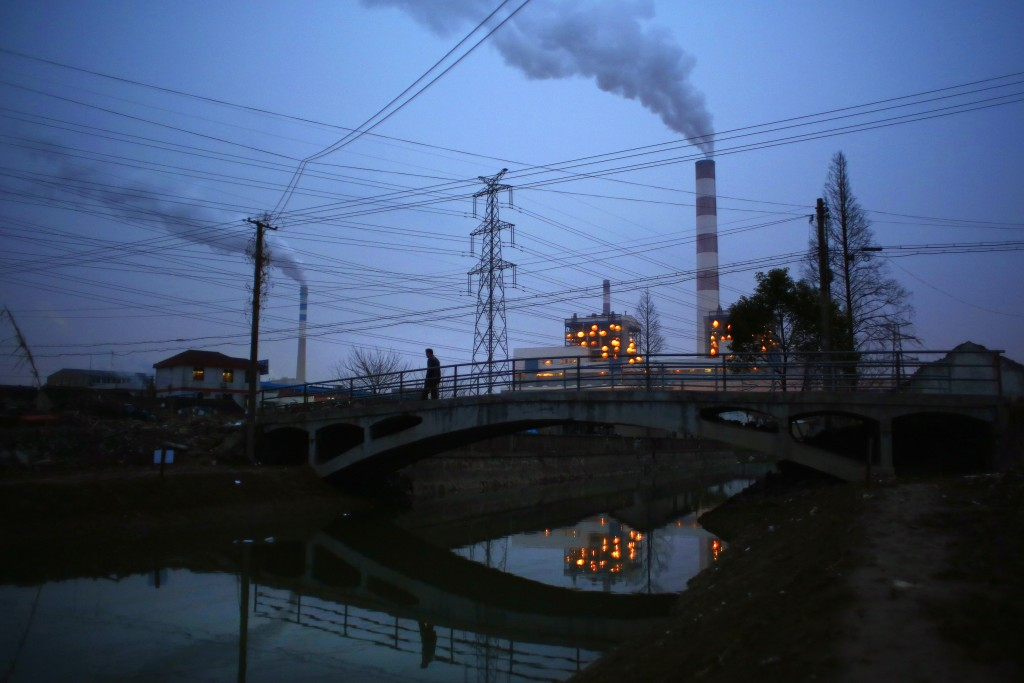 """A man walks over a bridge as smoke rises from chimneys of a thermal power plant in Shanghai February 23, 2015. Nearly 90 percent of China's big cities failed to meet air quality standards in 2014, but that was still an improvement on 2013 as the country's """"war on pollution"""" began to take effect, the environment ministry said on February 2, 2015. REUTERS/Carlos Barria  (CHINA - Tags: ENERGY ENVIRONMENT) - RTR4QT9B"""