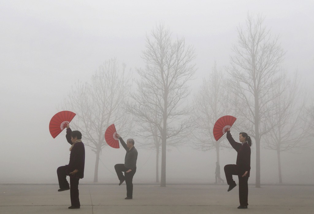 People do morning exercises on a polluted day in Jiaozuo, Henan province, March 16, 2015. Photo by China Daily/Reuters