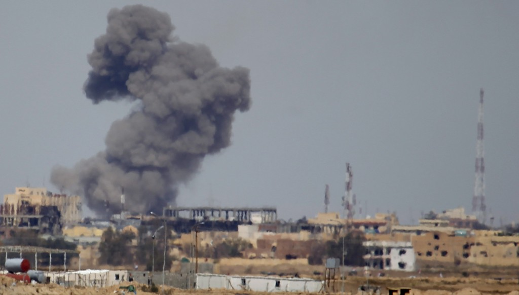 A plume of smoke rises above a building during an air strike in Tikrit March 27, 2015. The U.S. military is combining drone strikes with those of war planes. Photo By Thaier Al-Sudani/Reuters