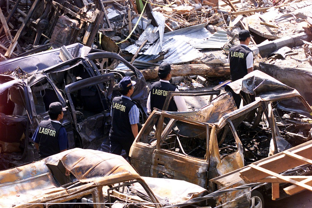 Indonesian forensic policemen walks past destroyed cars near a Bali bombing in 2002.  Photo By Beawiharta/Reuters.