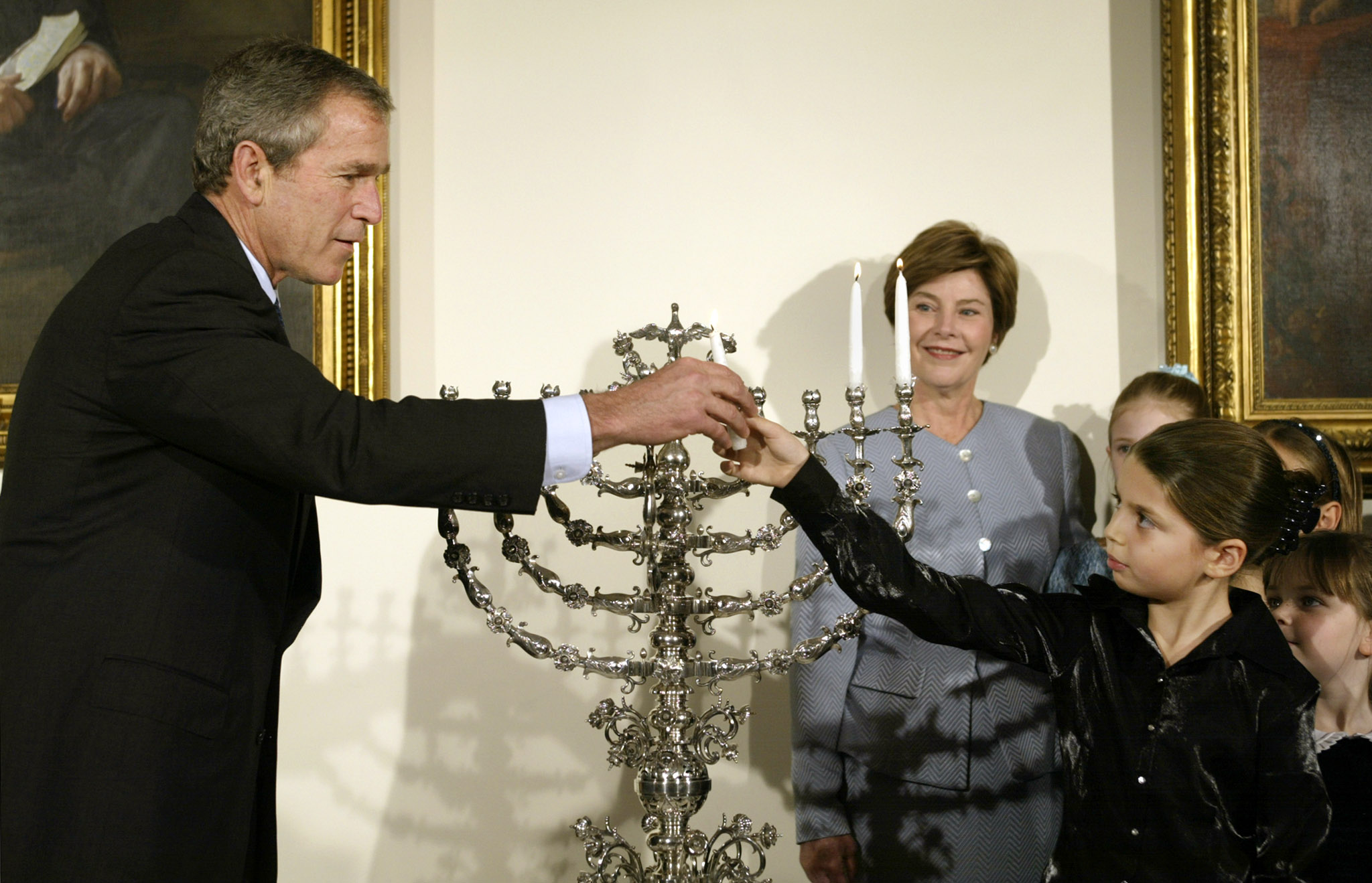 President George W. Bush joins eight-year-old Talia Lefkowitz as they light a hundred year-old menorah on loan from the Jewish Museum in New York during a Hanukkah reception in the White House December 10, 2001. Photo by Kevin Lamarque/Reuters