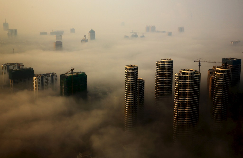 Buildings in construction are seen among mist during a hazy day in Rizhao, Shandong province, China, October 18, 2015. REUTERS/Stringer CHINA OUT. NO COMMERCIAL OR EDITORIAL SALES IN CHINA      TPX IMAGES OF THE DAY      - RTS4X6T