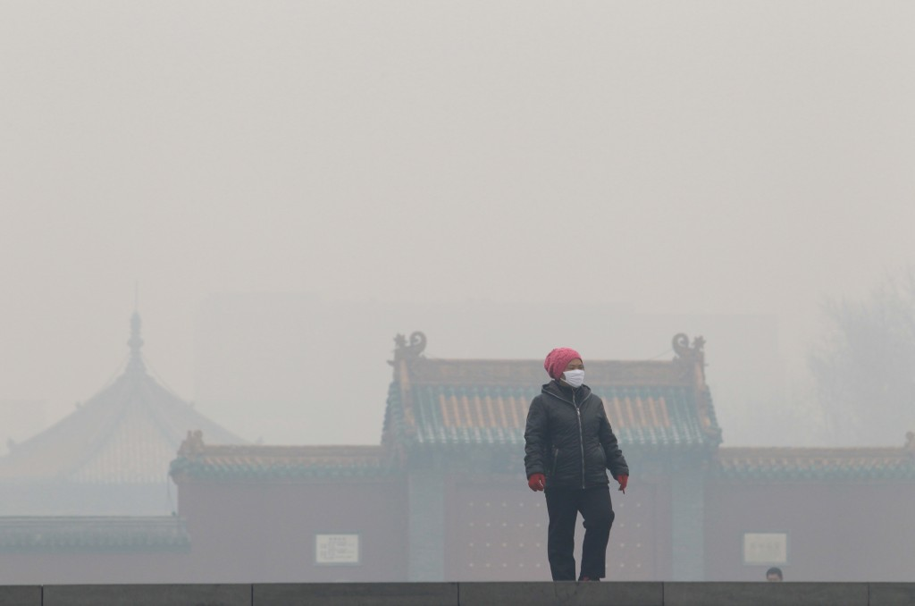 A woman wearing a mask walks outside the old palace museum on a hazy day in Shenyang, Liaoning province, November 8, 2015. As winter heating started in the city, the reading of PM2.5 was more than 1000 micrograms per cubic metre on Sunday, according to local media. Picture taken November 8, 2015. REUTERS/Stringer CHINA OUT. NO COMMERCIAL OR EDITORIAL SALES IN CHINA - RTS62Y6