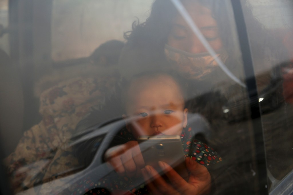 A baby is held inside a vehicle stranded on a highway between Beijing and Hebei province, China, that is closed due to smog on an extremely polluted day November 30, 2015. REUTERS/Damir Sagolj - RTX1WG4R