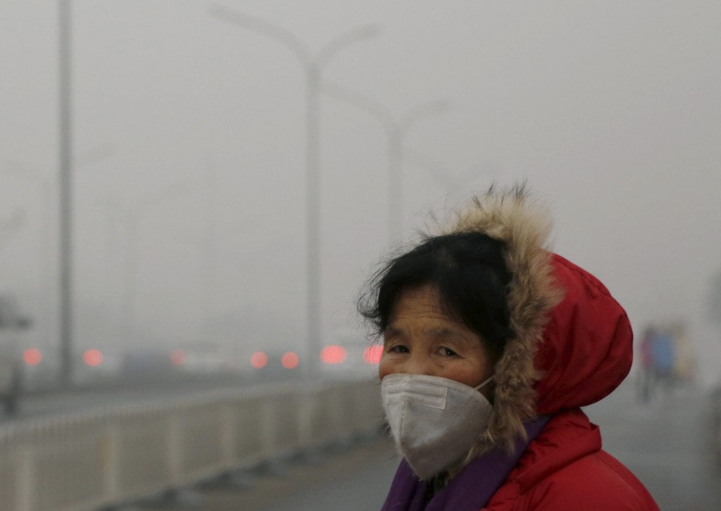 A woman wearing a protective mask makes her way on an extremely polluted day as hazardous, choking smog continues to blanket Beijing, China December 1, 2015. REUTERS/Kim Kyung-Hoon - RTX1WLZK