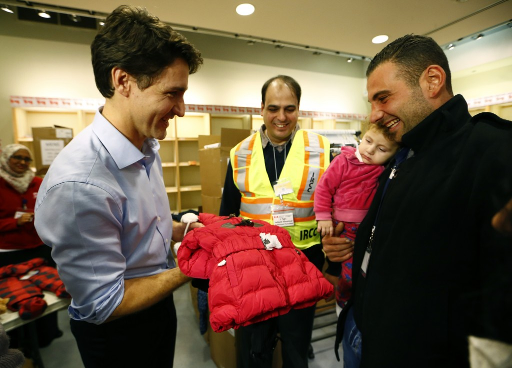 Syrian refugees are presented with a child's winter jacket by Canada's Prime Minister Justin Trudeau (L) on their arrival from Beirut at the Toronto Pearson International Airport in Mississauga, Ontario, Canada December 11, 2015. After months of promises and weeks of preparation, the first Canadian government planeload of Syrian refugees landed in Toronto on Thursday, aboard a military aircraft met by Prime Minister Justin Trudeau.  REUTERS/Mark Blinch  - RTX1Y6VA