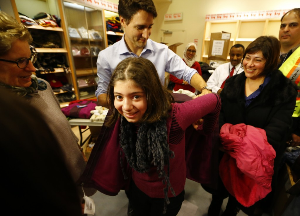 Canada's Prime Minister Justin Trudeau helps a young Syrian refugee try on a winter coat after she arrived with her family from Beirut at the Toronto Pearson International Airport in Mississauga, Ontario, Canada December 11, 2015. After months of promises and weeks of preparation, the first Canadian government planeload of Syrian refugees landed in Toronto on Thursday, aboard a military aircraft met by Prime Minister Justin Trudeau.  REUTERS/Mark Blinch  - RTX1Y6W6