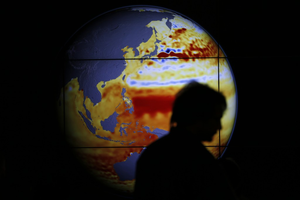 A woman walks past a map showing the elevation of the sea in the last 22 years during the World Climate Change Conference 2015 (COP21) at Le Bourget, near Paris, France, December 11, 2015. Photo by Stephane Mahe/REUTERS