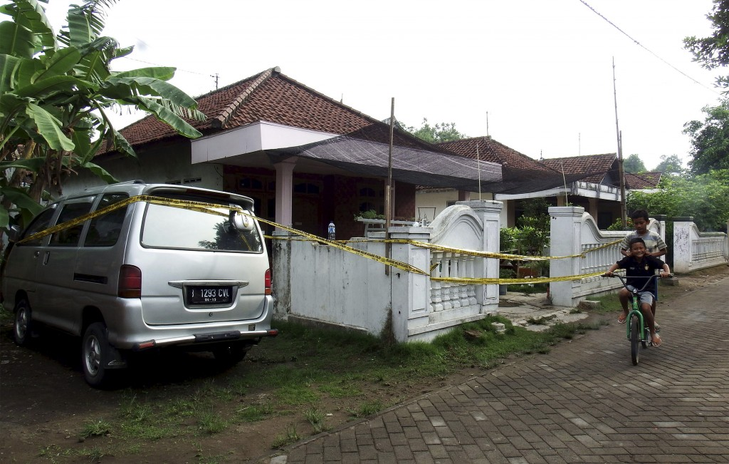 Children ride a bike past a house with police tape around it, following a raid by anti-terror police on the island of  Java, Sunday. Photo by Syaiful Arif via Reuters.