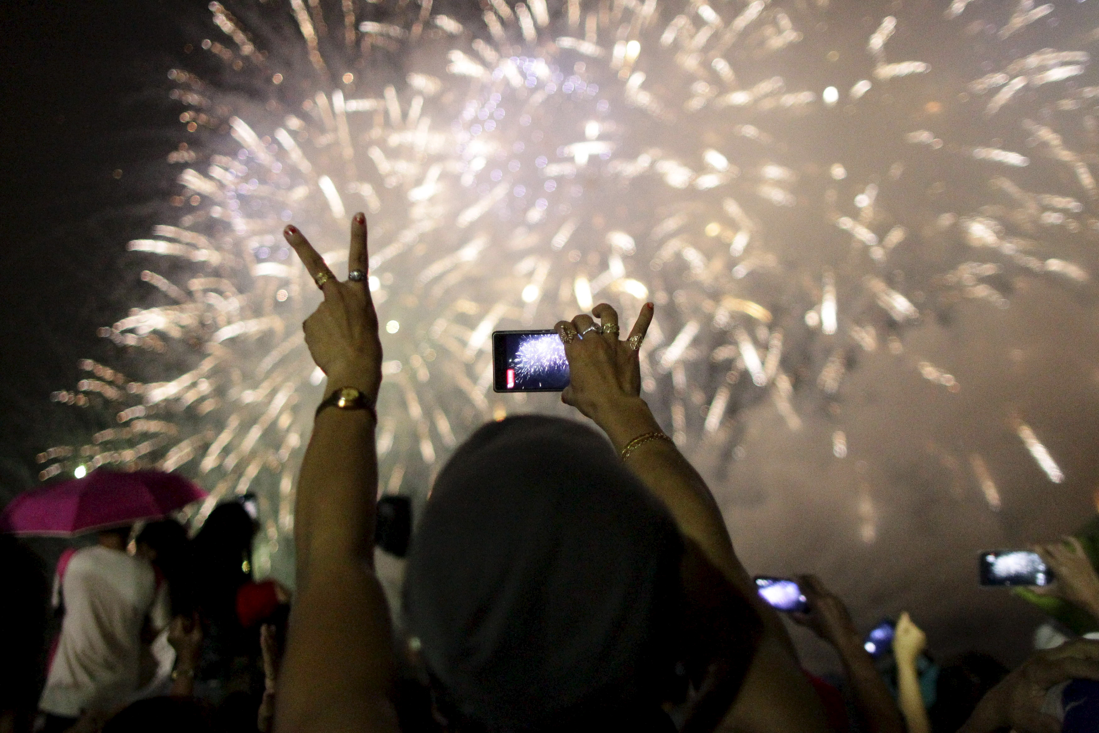 A reveler uses a mobile phone to take pictures of fireworks during a New Year celebration in Manila on Jan. 1, 2016.  Photo by Czar Dancel/Reuters
