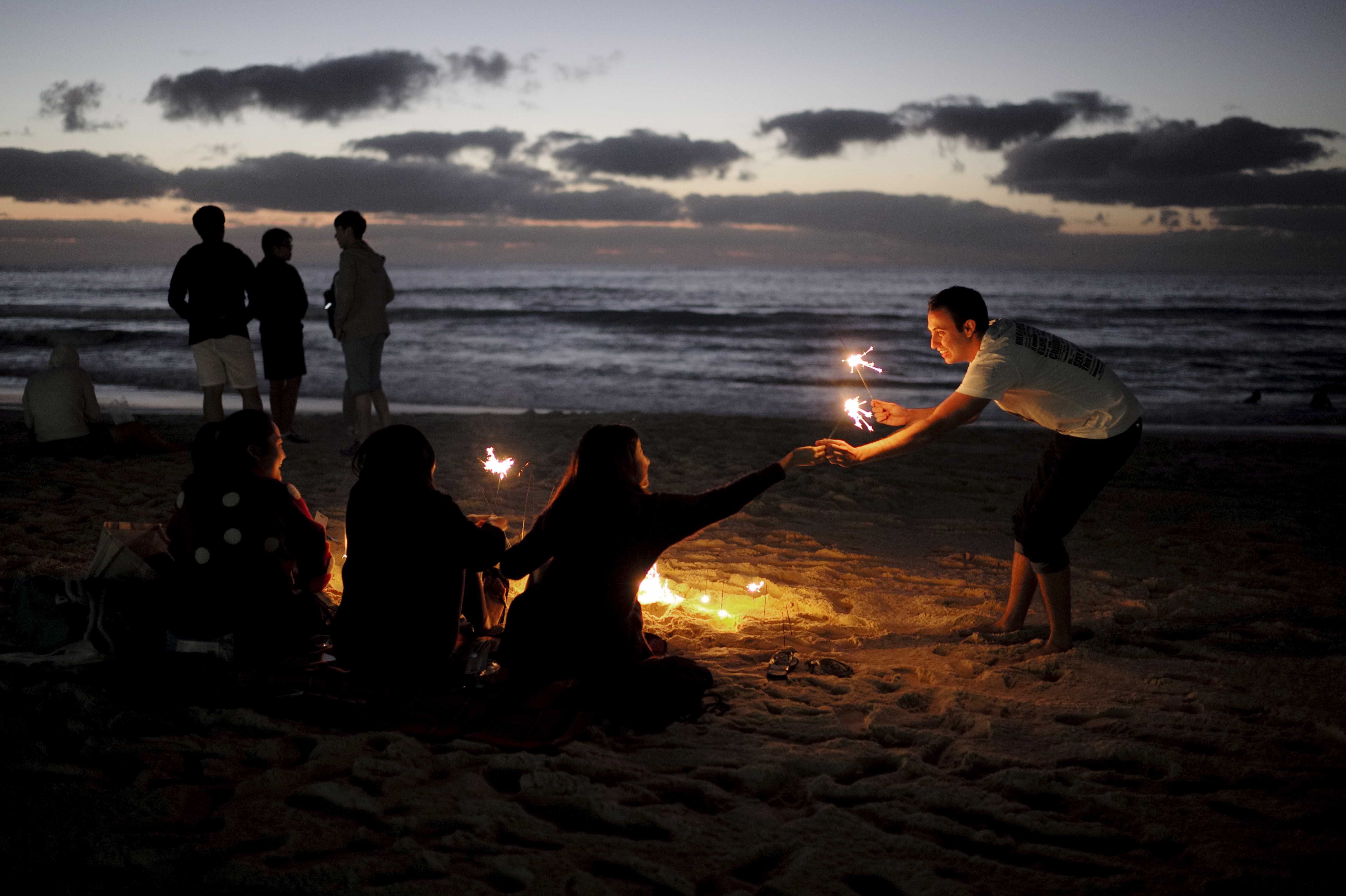 A New Year's reveller (R) receives a gift of sparklers as hundreds of partygoers await the first sunrise of the new year on Australia's Bondi Beach in Sydney. Photo by Jason Reed/Reuters