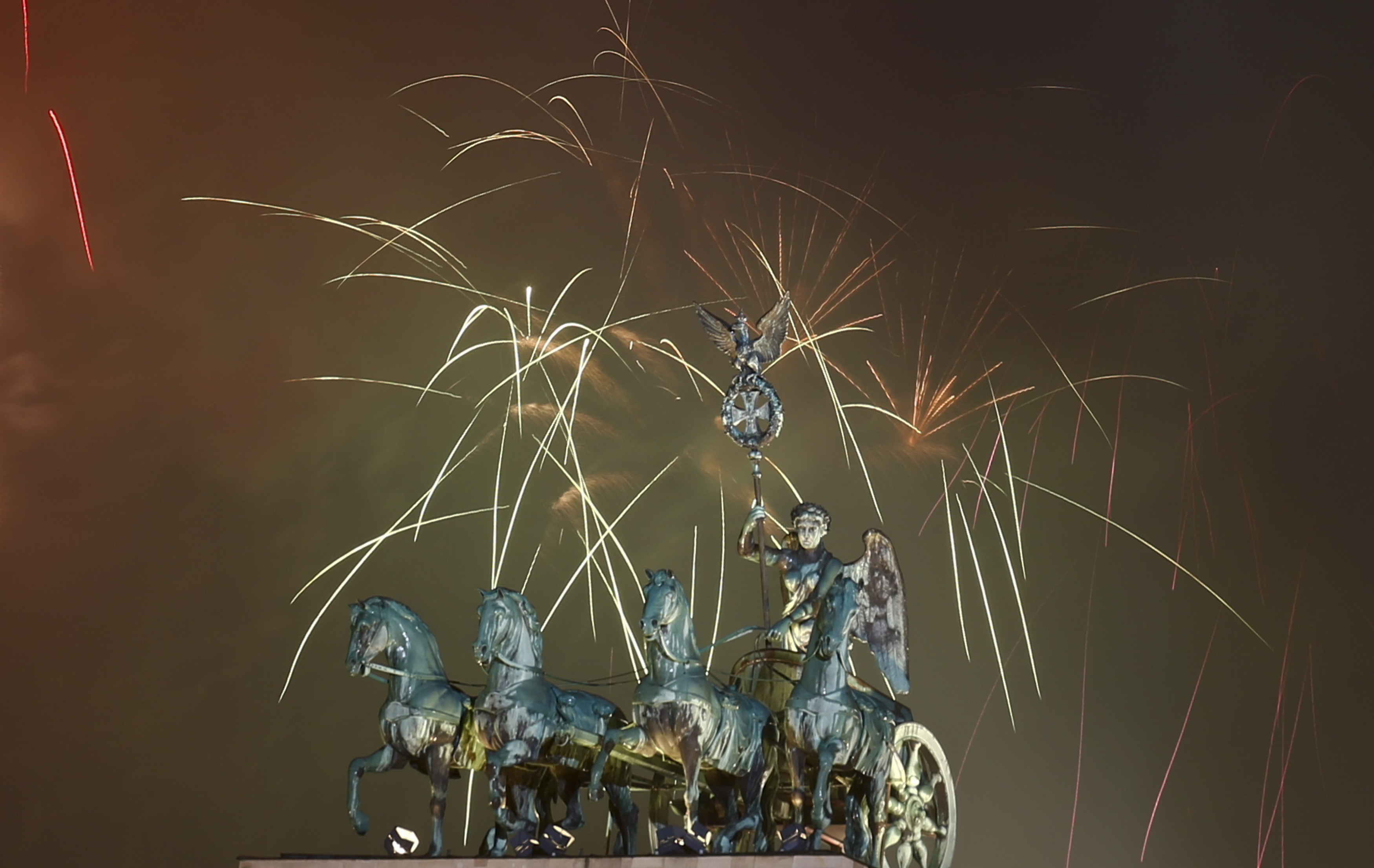 Fireworks explode next to the Quadriga sculpture atop the Brandenburg gate during New Year celebrations in Berlin, Germany.. Photo by Hannibal Hanschke/Reuters