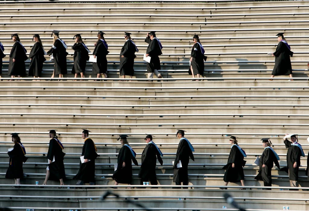 Students in black graduation regalia walking on steps.