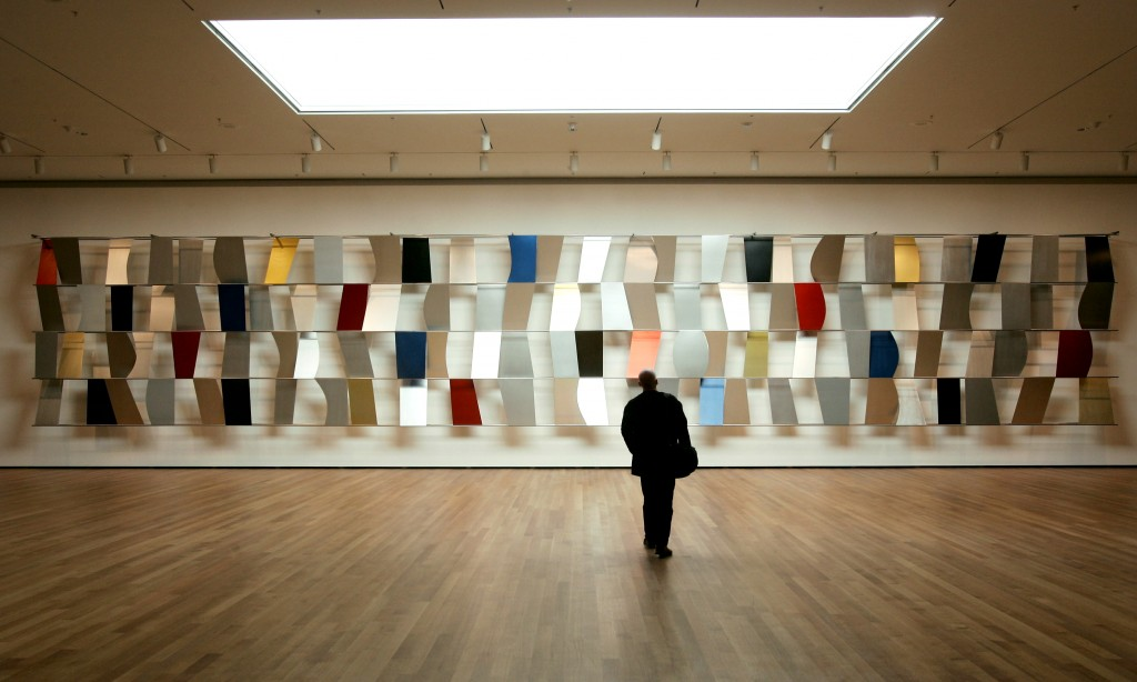 "A visitor walks towards Ellsworth Kelly's ""Sculpture For a Large Wall"" of anodized aluminum (1957) in the newly renovated Museum of Modern Art in New York City, November 15, 2004. The new museum, which stands between 53rd and 54th streets in Midtown Manhattan, was designed by Japanese architect Yoshio Taniguchi and nearly doubles the capacity of the former building. The Museum encompasses 630,000 square feet on six floors and cost $425 million to build. The reopening of the Museum to the public on November 20 will commemorate its 75th anniversary. - RTXN1TF"