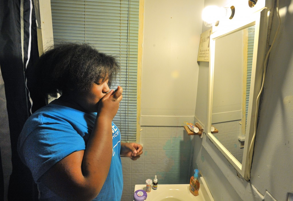 Cameron Carter, 12, takes eight medications every morning to deal with her asthma.  Studies show that childhood traumas such as household substance abuse, violence and poverty can trigger asthma. Image by Daniel Mears/ The Detroit News