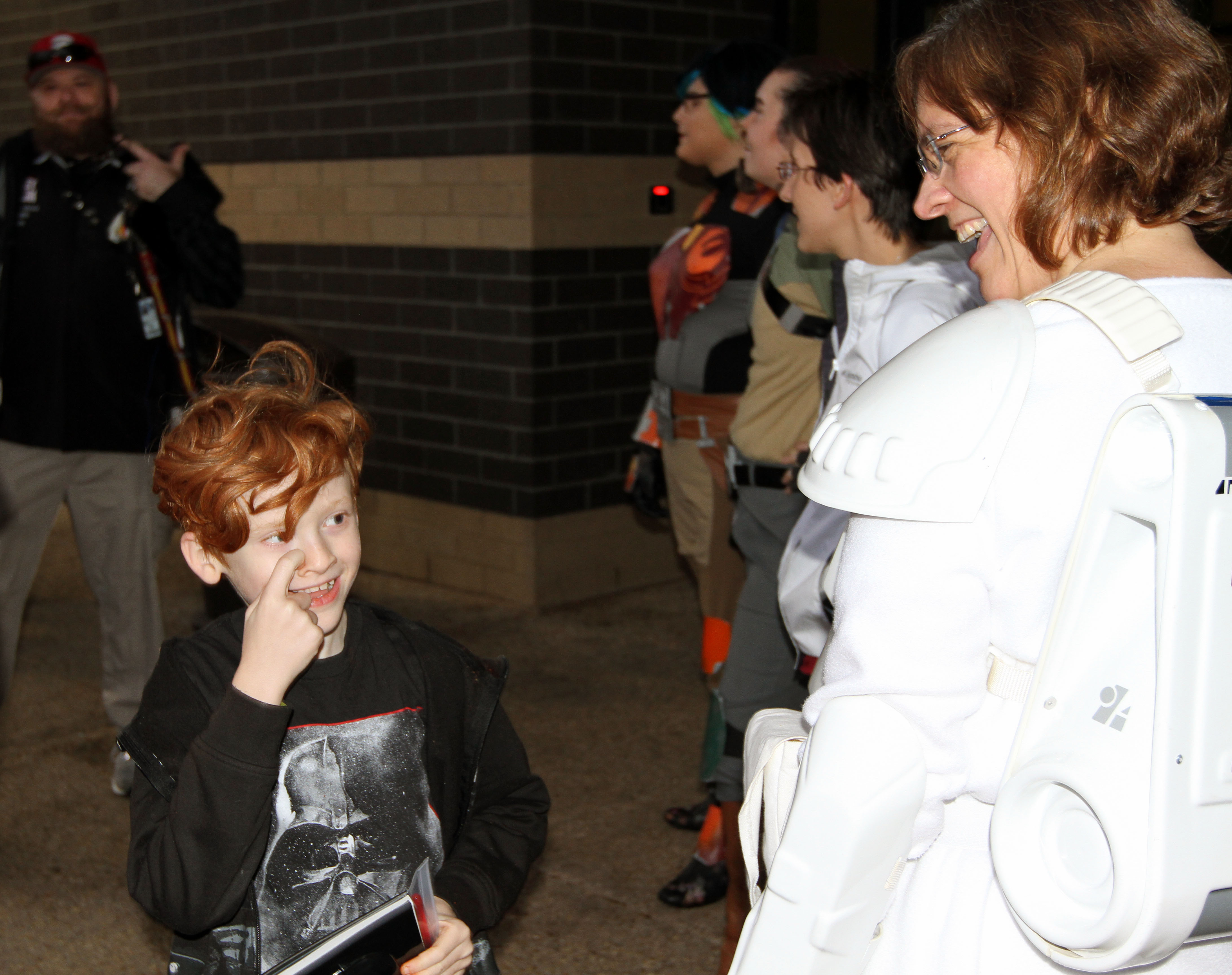 "A young ""Star Wars"" fan interacts with costumer Lori Frye at the Dec. 17 premiere of ""The Force Awakens"" at the Alamo Drafthouse Cinema in Ashburn, Va. The best part of costuming is the reaction from children, says Frye, but adults also revert back to their childhoods when they see a reminder of a beloved movie. Photo by Larisa Epatko"