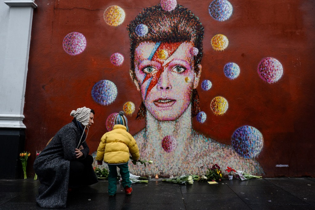 Floral tributes are left beneath a mural of David Bowie, painted by Australian street artist James Cochran, aka Jimmy C, following the announcement of the singer's death at age 69. Photo by Chris Ratcliffe/AFP/Getty Images