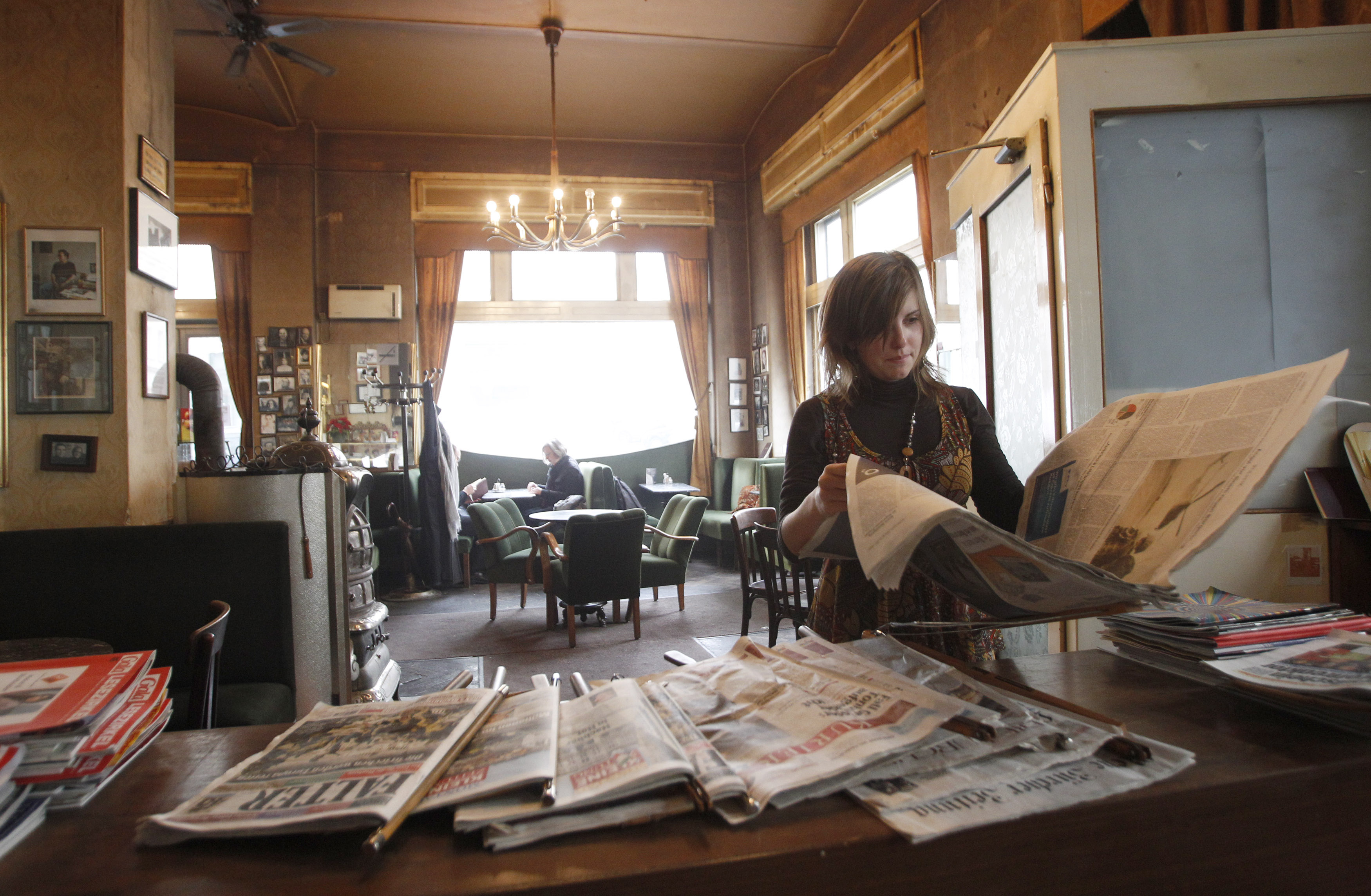 A woman reads a newspaper in the Viennese coffee house (Wiener Kaffeehaus) Jelinek in Vienna November 14, 2011. The UNESCO appointed the Viennese coffeehouse culture as an immaterial cultural heritage on November 10. Picture taken November 14, 2011.  REUTERS/Lisi Niesner (AUSTRIA - Tags: ENTERTAINMENT SOCIETY) - RTR2U1PT related words: cafe, newspaper, Vienna, Austria