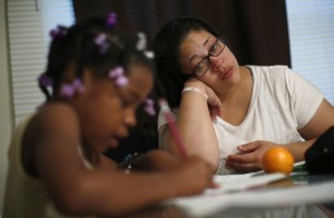 Delores Leonard (R) helps her daughter Erin with her homework at the breakfast table before heading to work at a McDonald's Restaurant in Chicago, Illinois, September 25, 2014. Leonard, a single mother raising two daughters, has been working at McDonald's for seven years and has never made more than minimum wage. Picture taken September 25, 2014. REUTERS/Jim Young (UNITED STATES - Tags: BUSINESS EMPLOYMENT TPX IMAGES OF THE DAY) - RTR4AK5P