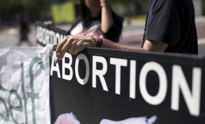 An activist holds a rosary while ralling against abortion outside City Hall in Los Angeles