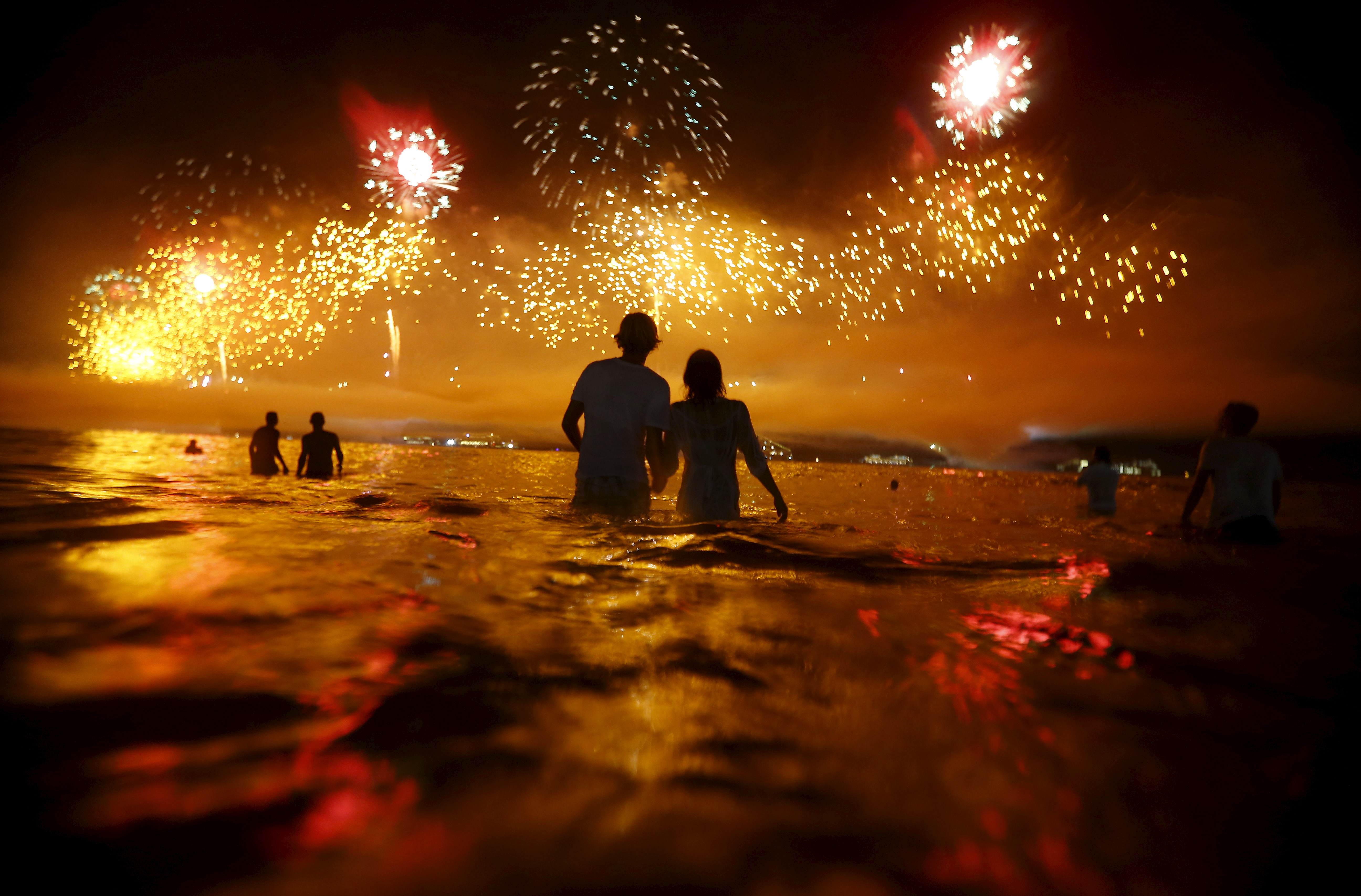 People watch as fireworks explode over Copacabana beach during New Year celebrations in Rio de Janeiro, Brazil. Photo by Ricardo Moraes/Reuters