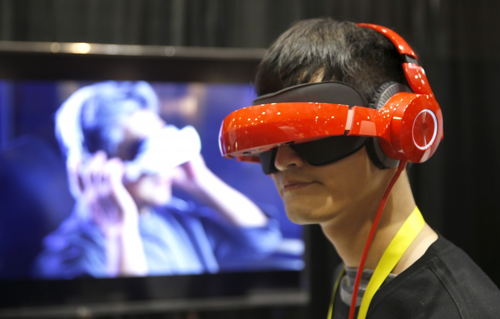 """Eric Yu of Royole models the company's foldable Smart Mobile Theater system during """"CES Unveiled,"""" a preview event of the 2016 International CES trade show, in Las Vegas, Nevada January 4, 2016. The $700.00 system has noise-canceling headphones and a viewing system that is vision correctable so you don't need to wear your glasses, Yu said.  REUTERS/Steve Marcus - RTX2121Z"""