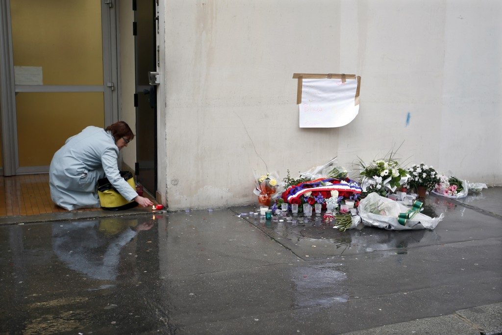 A woman lights a candle near a memorial to pay tribute to the victims of the January 2015 attacks outside the former offices of French weekly satirical newspaper Charlie Hebdo in Paris on Jan. 7. Photo by Charles Platiau/Reuters